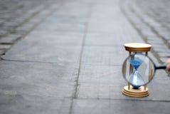 Blauw zandloper en vergrootglas op steenbestrating Royalty-vrije Stock Foto