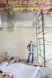 Blauwdrukken op lijst voor medio volwassen architect die plafond bekijken royalty-vrije stock fotografie