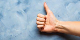 Blauwe achtergrond met omhoog de duim van de vrouwen` s hand Royalty-vrije Stock Foto's