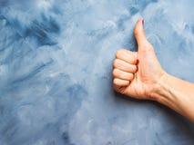 Blauwe achtergrond met omhoog de duim van de vrouwen` s hand Royalty-vrije Stock Afbeeldingen