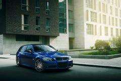 Blauwe auto BMW 5 reekse90/e91 verblijf op asfaltweg in de stad Moskou bij dag Stock Fotografie
