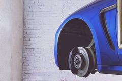 Blauwe auto in het benzinestation voor band, opschorting en remmen stock foto