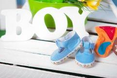Blauwe babyschoenen en bloemen Stock Afbeeldingen