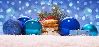 Blauwe ballen en Kerstmiskoekjes op sneeuw Stock Foto's