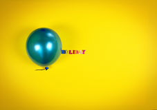 Blauwe ballon en inschrijvingsvakantie op een gele oppervlakte Royalty-vrije Stock Fotografie