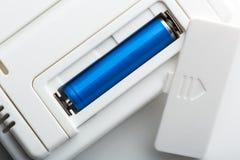 Blauwe batterij in de contactdoos Stock Foto's
