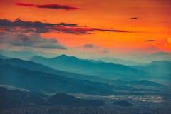 Blauwe bergketen en oranje zonsondergang bewolkte hemel royalty-vrije stock foto