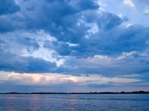 Blauwe betrokken hemel over meer Stock Foto's