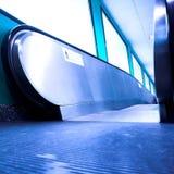 Blauwe bewegende roltrap in de bureauzaal Stock Afbeeldingen
