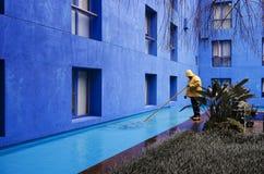Blauwe binnenplaats - gele oliejas Stock Foto