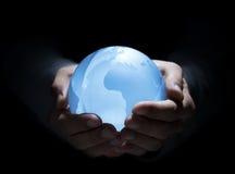 Blauwe bol in menselijke handen royalty-vrije stock afbeeldingen