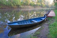 Blauwe boot op rivier Stock Afbeeldingen
