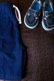 Blauwe bootschoenen in borrels op bruine houten achtergrond Jongensuitrusting Hoogste mening De ruimte van het exemplaar Stock Fotografie