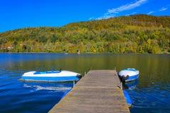 Blauwe boten bij pier voor meertros - kleurrijk de herfstmeer Royalty-vrije Stock Foto's