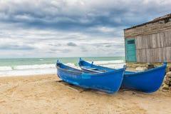 Blauwe boten op de kust in een winderige dag Stock Foto's