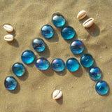 Blauwe brieven in het zand - A - verticaal stock fotografie
