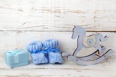 Blauwe buiten voor de baby op een houten achtergrond van blauwe giftdoos met satijnlint en houten paard Royalty-vrije Stock Afbeeldingen