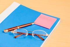 Blauwe bureauomslag, glazen en pen Selectieve nadruk Stock Fotografie