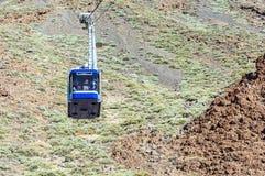 Blauwe cabinekabelwagen met toeristen die kabels beklimmen die aan t worden uitgerekt Stock Foto's