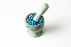Blauwe capsules en oranje pillen met mortierstampers op witte achtergrond Stock Foto
