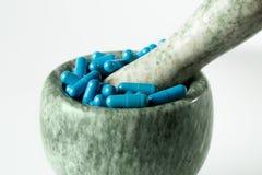 Blauwe capsules en oranje pillen met mortierstampers op witte achtergrond Royalty-vrije Stock Afbeeldingen