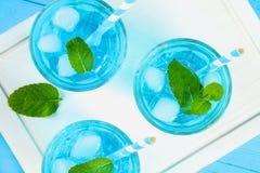 Blauwe cocktail met ijs en munt in glazen op een witte houten raad op een blauwe lijst Hoogste mening royalty-vrije stock foto