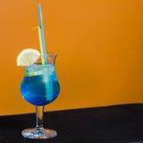 Blauwe cocktail op oranje achtergrond Royalty-vrije Stock Fotografie