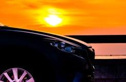 Blauwe compacte die SUV-auto met sport en luxeontwerp op betonweg door het overzees bij zonsondergang wordt geparkeerd r stock foto's