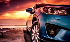 Blauwe compacte die SUV-auto met sport, moderne, en luxeontwerp op betonweg door het overzees bij zonsondergang wordt geparkeerd  royalty-vrije stock afbeelding