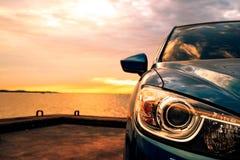 Blauwe compacte SUV-auto met sport en modern die ontwerp op betonweg door het overzees bij zonsondergang wordt geparkeerd Milieuv stock foto