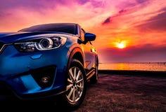 Blauwe compacte SUV-auto met sport en modern die ontwerp op betonweg door het overzees bij zonsondergang wordt geparkeerd stock afbeeldingen