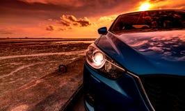 Blauwe compacte SUV-auto met sport en modern die ontwerp op betonweg door het overzees bij zonsondergang wordt geparkeerd Milieuv royalty-vrije stock foto's