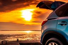 Blauwe compacte SUV-auto met sport en modern die ontwerp op betonweg door het overzees bij zonsondergang wordt geparkeerd De reis stock foto