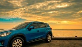Blauwe compacte SUV-auto met sport en modern die ontwerp op betonweg door overzees bij zonsopgang wordt geparkeerd Milieuvriendel stock fotografie