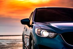 Blauwe compacte SUV-auto met sport en modern die ontwerp op het strand door het overzees bij zonsondergang wordt geparkeerd Milie stock fotografie