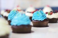 Blauwe cupcakes met bestrooit op witte lijst royalty-vrije stock afbeelding