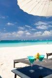 Blauwe Curacao cocktail met plak van ananas op wit strand stock afbeelding