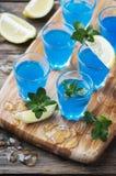 Blauwe curacao likeur met citroen op de houten lijst stock fotografie