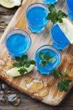 Blauwe curacao likeur met citroen op de houten lijst royalty-vrije stock foto's