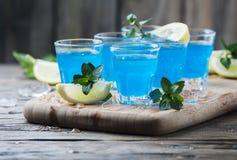Blauwe curacao likeur met citroen op de houten lijst royalty-vrije stock afbeeldingen