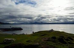 Blauwe de herfstfjord, mens op parkbank en boot stock foto's