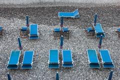 Blauwe deckchairs op steenachtig strand Royalty-vrije Stock Afbeeldingen