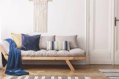 Blauwe deken en kussens op beige houten bank in wit zolderbinnenland met deur Echte foto stock foto