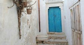 Blauwe deur tegen witte muur stock afbeelding