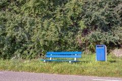 Blauwe die bank van hout en beton wordt gemaakt en een blauwe huisvuilbak voor een achtergrond van groen gebladerte stock foto