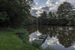 Blauwe die boot bij de bank van de rivier wordt vastgelegd stock fotografie