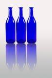 Blauwe die flessen met bezinning op witte achtergrond wordt geïsoleerd Stock Foto