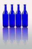 Blauwe die flessen met bezinning op witte achtergrond wordt geïsoleerd Stock Foto's