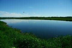 Blauwe die hemel in de rivier wordt weerspiegeld Royalty-vrije Stock Afbeeldingen