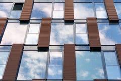 Blauwe die hemel in spiegelvensters wordt weerspiegeld van de moderne bureaubouw Stock Foto's